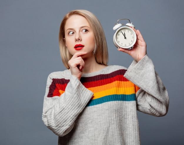 회색에 알람 시계와 스웨터에 아름 다운 금발