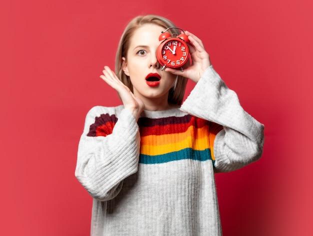 빨간색에 알람 시계와 스웨터에 아름 다운 금발