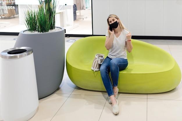 美しいブロンドは、モールのデザイナーの椅子に座って電話で話している。コミュニケーションとショッピング。休息と喜び。個人用保護具。パンデミックの場合の注意事項。