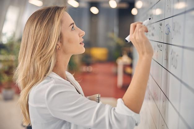 Красивая блондинка женщина держит маркер и изучает информацию на доске планировщика на работе