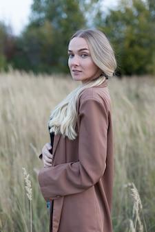 Красивая блондинка в пшеничном поле на закате стоит и смотрит в камеру.