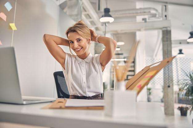 Красивая блондинка дама улыбается, укладывая волосы в офисе