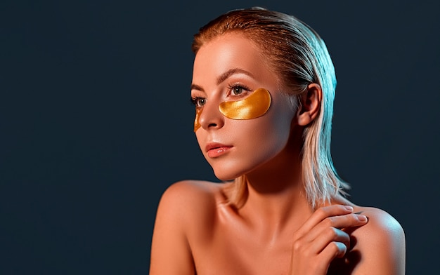 Beautiful blonde lady with gold eye patches.