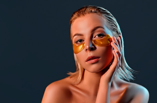 Beautiful blonde lady with gold eye patches