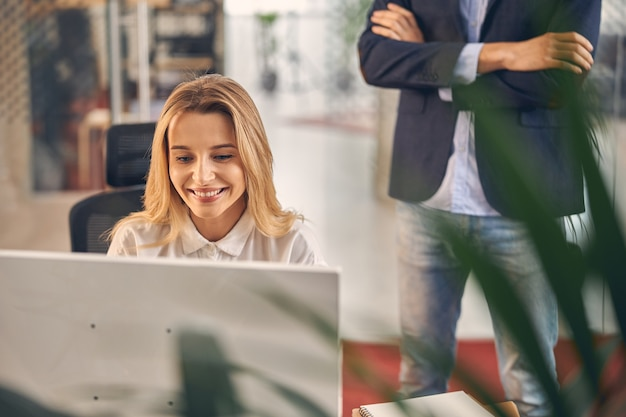 Beautiful blonde lady working on desktop pc and smiling while male colleague standing behind her