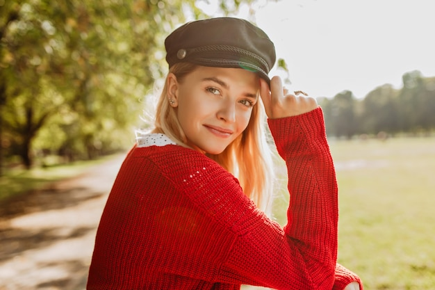 Beautiful blonde looking pretty in red pullover and trendy black hat standing in the park. smiling girl enjoys sunny autumn day.