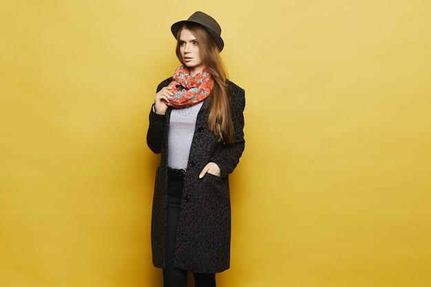 Красивая белокурая модель девушки в модном пальто с леопардовыми узорами, в модной шапке и красочном шарфе позирует. концепция осенней уличной моды