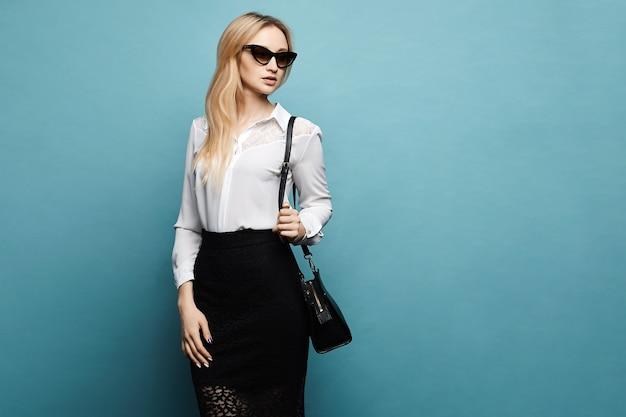 スタイリッシュなサングラス、白いブラウス、分離された青の背景にポーズをとって黒のタイトなスカートで美しい金髪のモデルの女の子