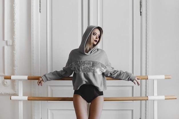 그녀의 머리에 후드와 란제리와 까마귀에 밝은 화장과 아름다운 금발 모델 소녀, 안무 바레에 기대어 서