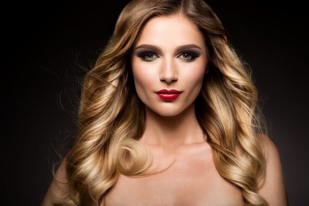 Beautiful blonde model girl with long curly hair . hairstyle wavy curls . red lips.