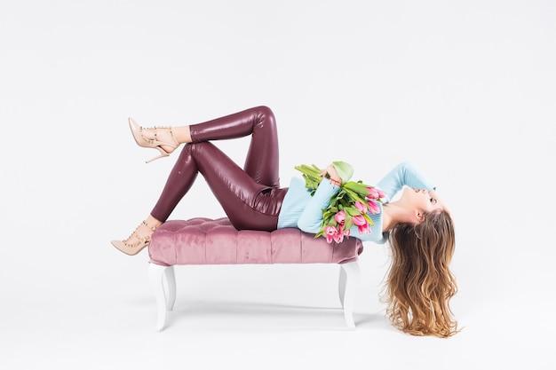 Bella modella bionda che tiene un mazzo di tulipani rosa