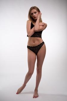 Красивая блондинка модель в черном кружевном нижнем белье позирует на белой стене.