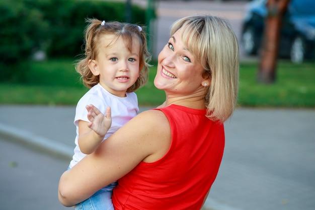 彼女の娘と一緒に赤いtシャツを着た美しい金髪のお母さん。グループポートレート