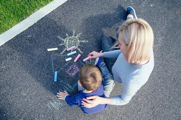 Красивая блондинка мать и ее милый маленький сын, нарисованные цветными мелками на асфальте в парке на фоне зеленой травы, вид сверху
