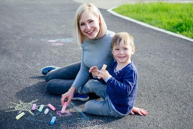Красивая блондинка мать и ее милый маленький сын нарисованы цветными мелками на асфальте в парке на фоне зеленой травы.