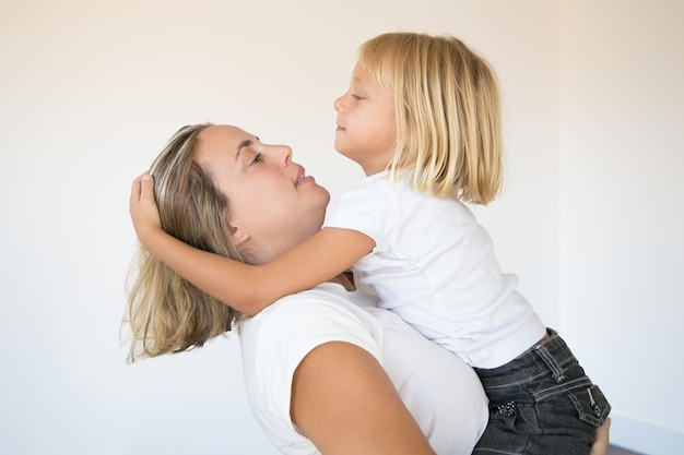 娘を抱いて彼女を見ている美しいブロンドの母親