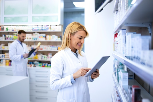 Beautiful blonde pharmacist typing on tablet computer and selling medicine online in drugstore.