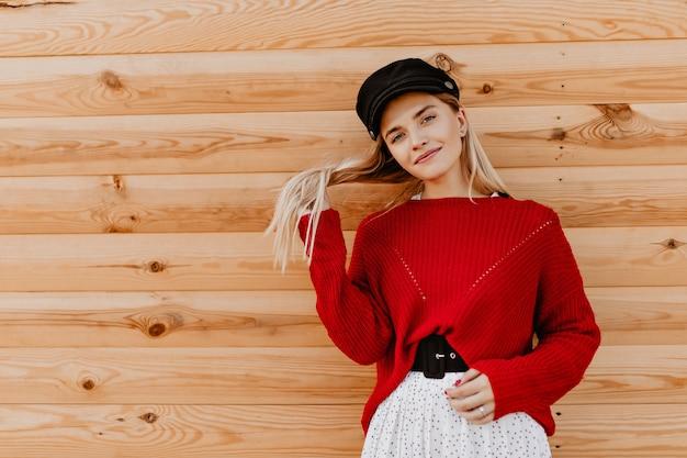 木造住宅の近くで髪をいじる美しいブロンド。外で暖かい秋の日を楽しんでいる魅力的な女の子。