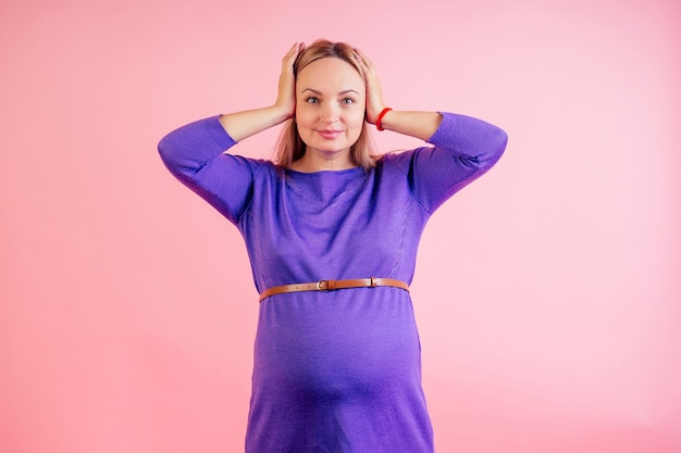 Beautiful blonde pregnant woman in a violet dress with big baby bump offended and upset headache in the studio on a pink background