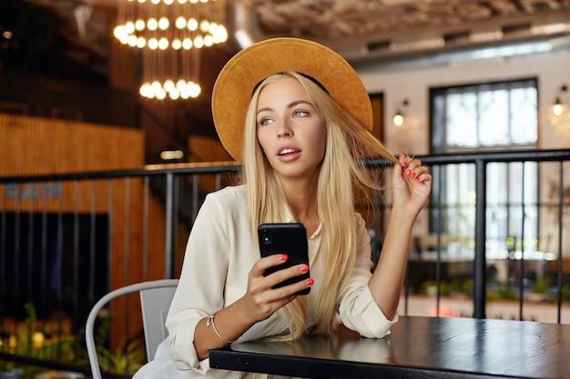 Красивая блондинка симпатичная женщина в шляпе позирует над рестораном во время обеденного перерыва с мобильным телефоном в руке, задумчиво глядя в сторону и трогая ее волосы