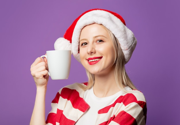 Beautiful blonde in red jacket and christmas hat on purple background
