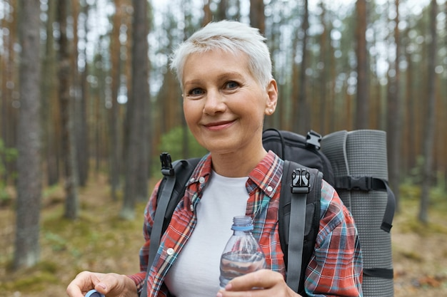 Beautiful blonde retired female spending vacations outdoors, walking in forest with rucksack behind her back, holding plastic bottle of water