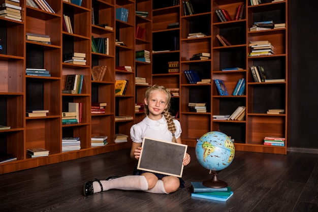 A beautiful blonde schoolgirl in uniform is sitting with a slate and a globe in the school classroom