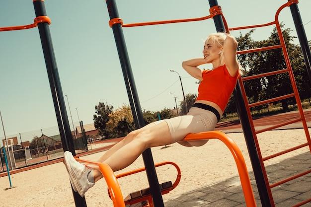 Красивая блондинка качает мускулами пресса на турниках