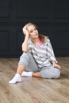 Красивая блондинка сидит на деревянном полу