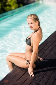 Beautiful blonde sitting on pools edge in a sunny day