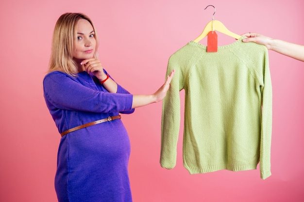 Beautiful blonde smiley pregnant woman big baby bump chooses a sweater on sale in the studio on a pink background . shopaholicism concept