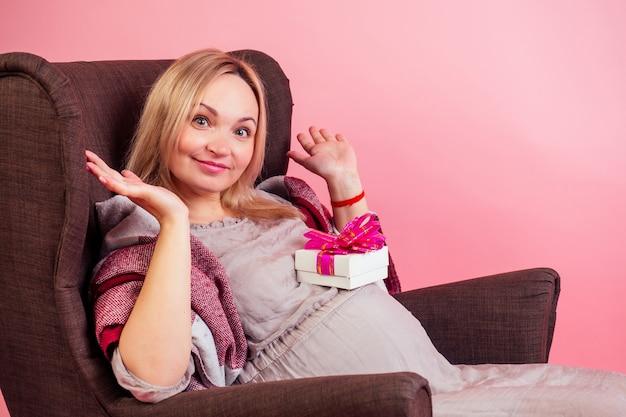 暖かい毛布で覆われた快適な椅子に座っている美しい金髪のスマイリー妊婦の大きな赤ちゃんのバンプは、ピンクの背景にスタジオでギフトボックスを受け取りました。コンセプトベビーシャワー。
