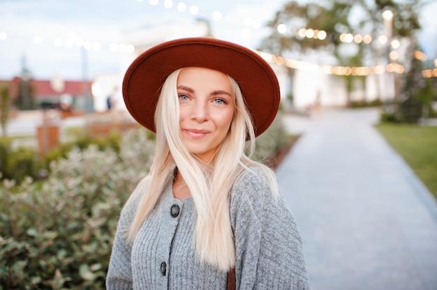 美しい金髪の笑顔の女の子はカジュアルな服と帽子を着用します