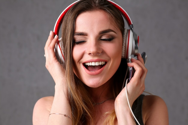 Beautiful blonde smiling woman with eyes closed wearing headphones listening favourite music on grey background. modern urban life audio book radio having moments with dance move concept