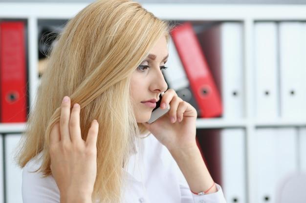 Beautiful blonde thoughtful businesswoman talk cellphone
