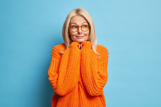 Beautiful blonde thoughtful middle aged woman keeps hands under chin and thinks deeply about something looks aside pensively wears spectacles knitted orange jumper.