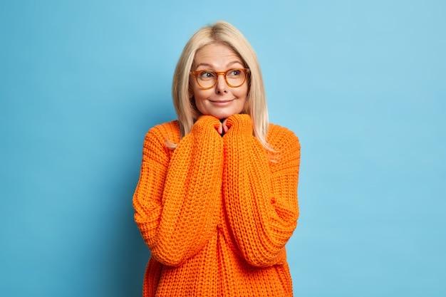 Красивая блондинка задумчивая женщина средних лет держит руки под подбородком и глубоко думает о чем-то, задумчиво смотрит в сторону, носит очки, связанный оранжевый джемпер.