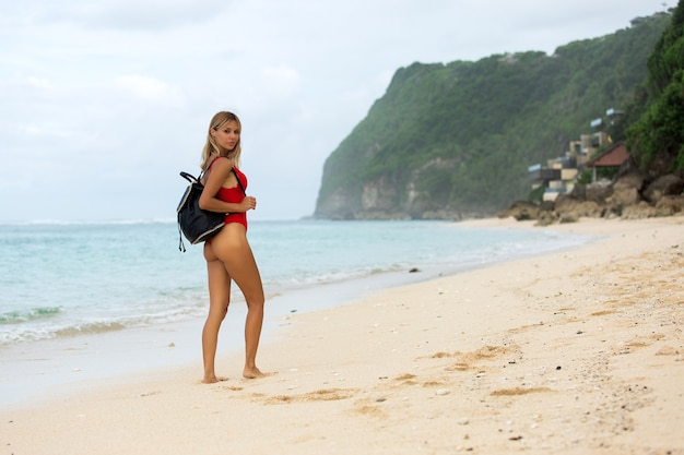 Beautiful blonde walks along the beach
