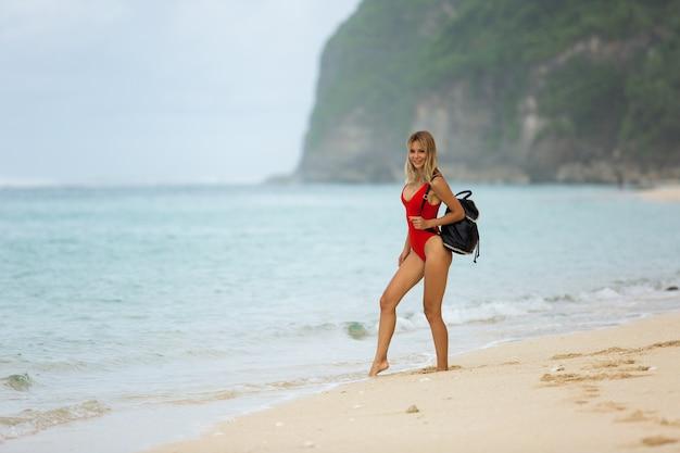 Красивая блондинка гуляет по пляжу