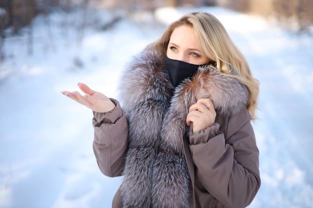 공원에서 겨울에 검은 보호 마스크에 모피 칼라와 아름다운 금발