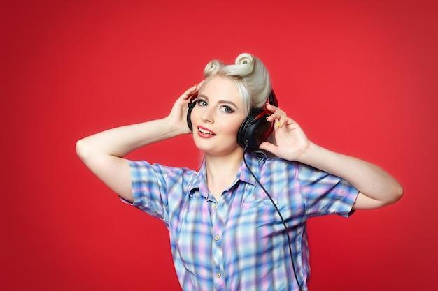 Красивая блондинка с наушниками позирует на красном фоне