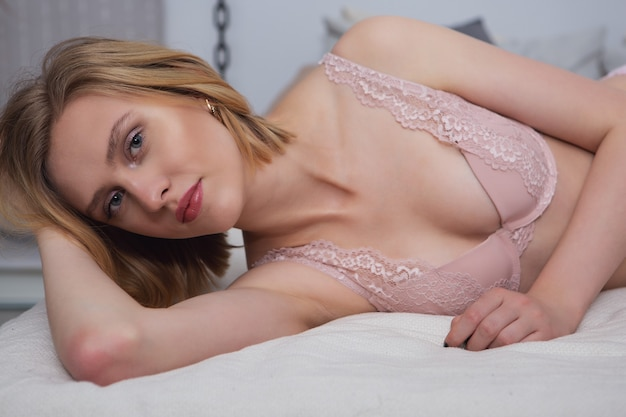 Beautiful blonde with a slight smile in pink lace lingerie lying on the bed