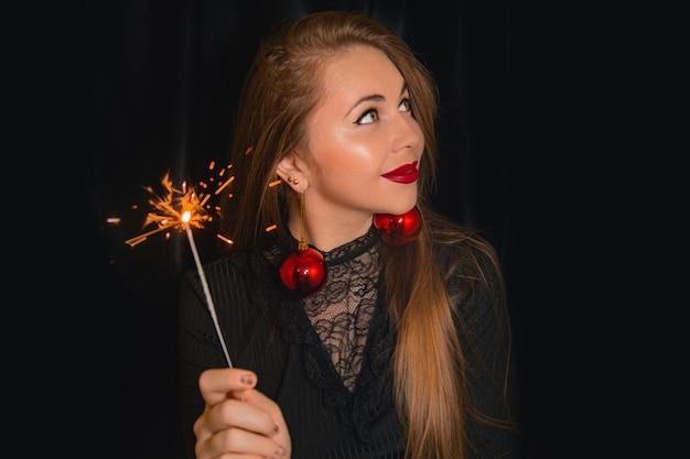 Красивая блондинка с бенгальскими огнями на черном фоне. концепция праздника. новый год.