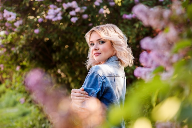 Beautiful blonde woman among the blooming trees, lilac flowers. spring spirit.