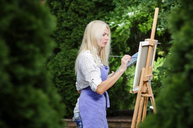 彼女の手にブラシを持つ美しい金髪の女性アーティストは、庭の帆布に描きます。