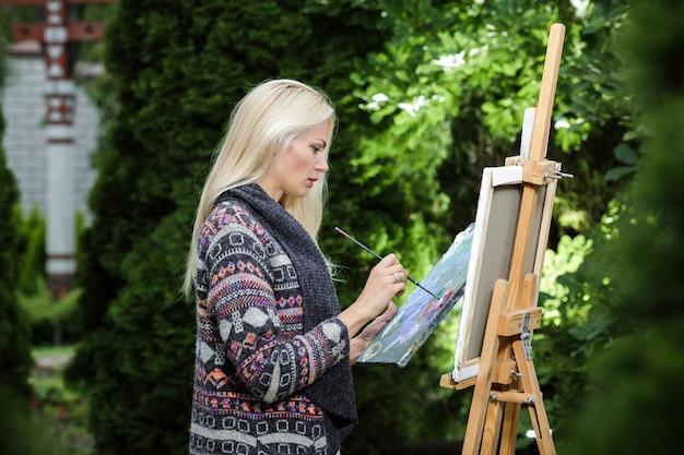 彼女の手にブラシを持つ美しい金髪の女性アーティストは、自然の中でキャンバスに描きます。