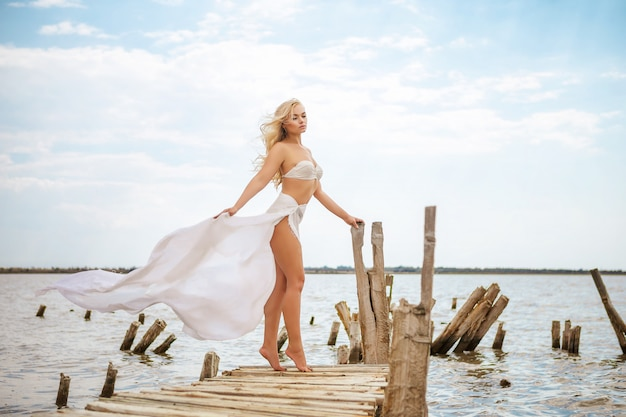 Beautiful blonde woman on the beach in a white swimsuit