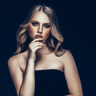黒の背景の上に完璧なメイクと髪型を持つ美しいブロンドの女性の美容モデルの女の子。