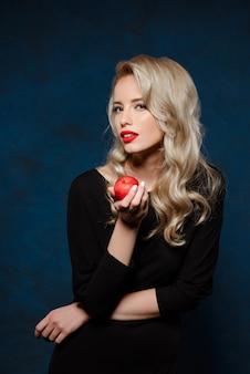 Bella donna bionda nella mela nera della tenuta del vestito