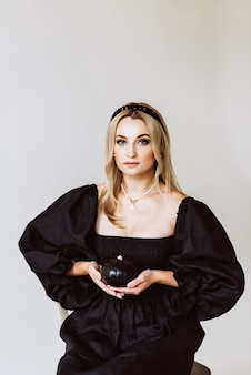 Beautiful blonde woman in a black linen dress with a pumpkin in her hands. ethnic fashion, natural fabric. halloween party. soft selective focus.